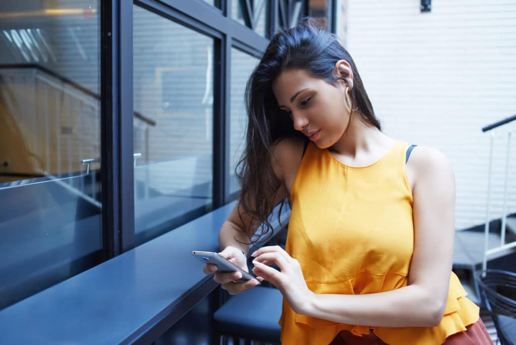 Young beautiful woman chatting on cell telephone while sitting in coffee shop interior during free time, charming female with long brunette hair browsing wifi via smart phone while relaxing in cafe